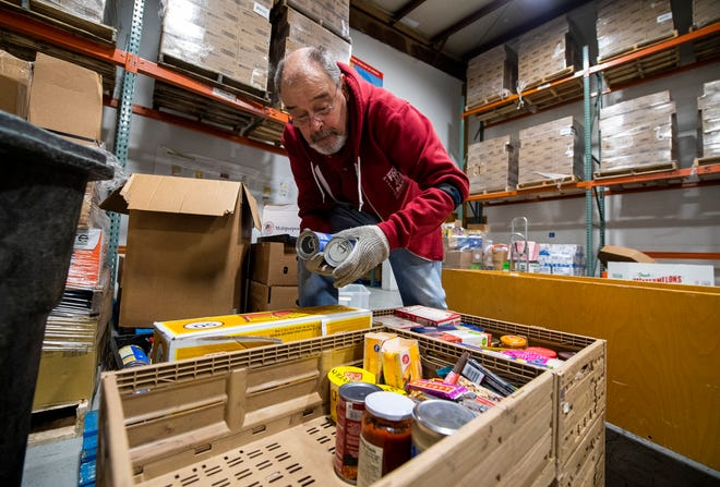 Trevor Jones unpacks donated items Tuesday at Hoosier Hill Food Bank. (Rich Janzaruk / Herald-Times)