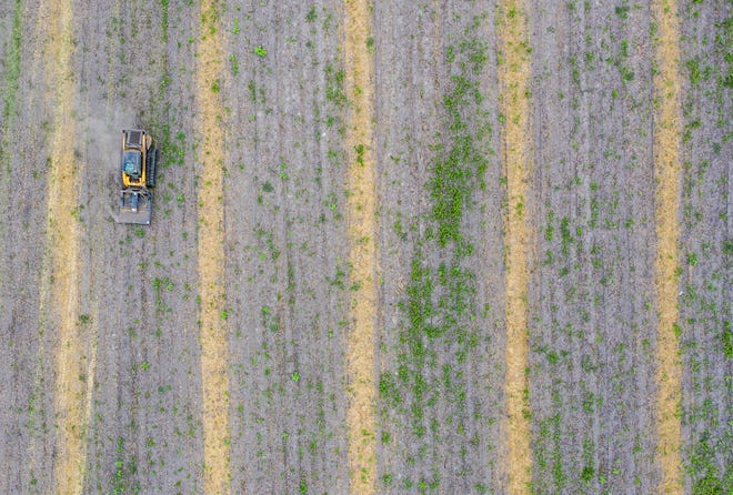 A tractor drives on a field off Bittersweet Road on Thursday, July 30, 2020, in Granger.