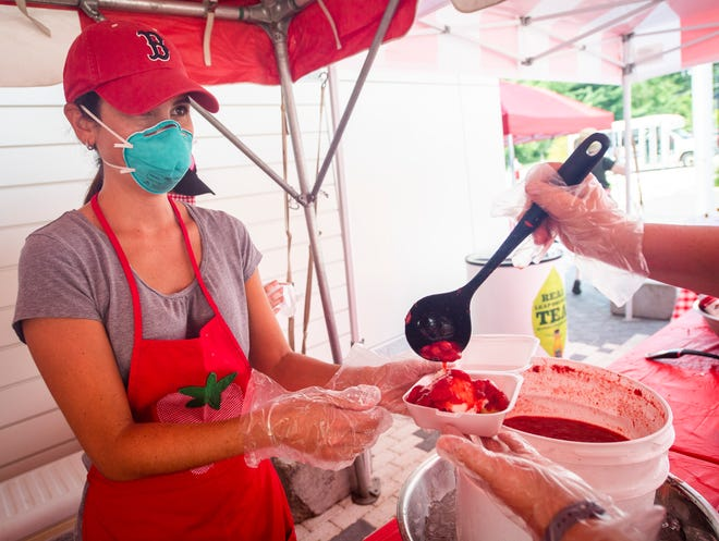 Kate Miller holds the container as Heather Groves pours on the strawberry topping last year during the Auxiliary to the Boys and Girls Club of Bloomington's 34th Annual Strawberry Shortcake Festival at Switchyard Park. All proceeds benefited the local clubs. (Rich Janzaruk / Herald-Times)