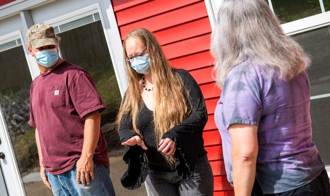 House Director Katie Norris, center, discusses plans May 6 with House Manager Harry Collins, left, and House Mom Heather Lake, right, at Robin &Trisha's House, a transitional home for those experiencing homelessness.