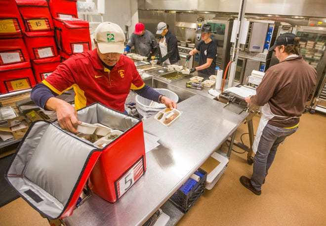 REAL Services director George Hawthorne, left, works with an assembly line of workers inside the Real Services kitchen to prepare and package Meals on Wheels dinners in South Bend. REAL Services is looking for volunteers to help deliver the meals.