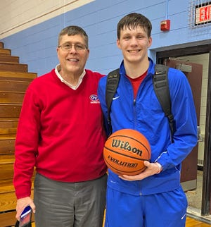 LEFT: During Tuesday night's varsity boys' basketball contest at Shakamak, Owen Valley senior Stephen Atkinson solidified his name in the Patriot record books as the all-time leading scorer. The record, previously held by 1985 graduate Greg Wright, was 1,699 points. Atkinson started the night trailing the record by just three points at 1,696. The first two points scored by Atkinson Tuesday night was a lay-up with an assist from Zane Sparks. After getting fouled a bit later in the first quarter, Stephen hit this first free throw to tie the record at 1,699 and hit the subsequent second to break the record, bringing the Owen Valley bench and crowd to their feet in applause. Atkinson went on to score an additional 24 points on the night, bringing his current point total to 1,724. Congratulations Stephen on a phenomenal accomplishment! Stephen is pictured with Owen Valley head coach Roger Fleetwood after the 51-48 win over the Lakers after being presented the game ball. (Amanda York / Spencer Evening World)