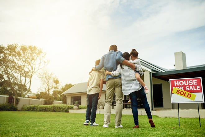 A family stands in the front yard of a home for sale