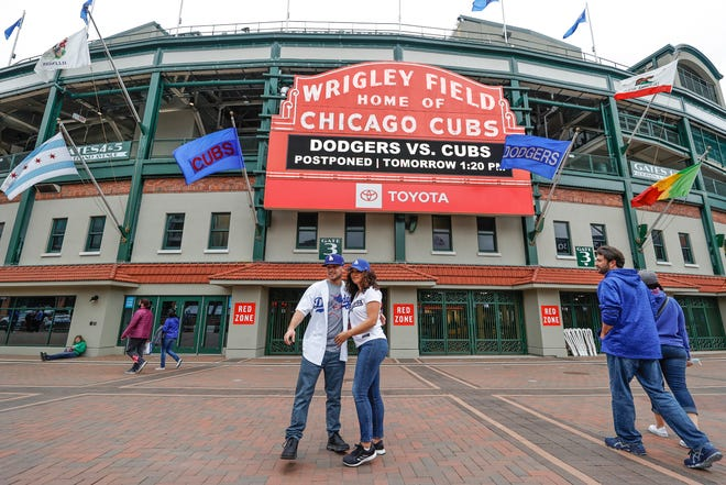 Los Angeles Dodgers fans Carlos Cativo and Nicole Ramos pose for a picture outside the Wrigley Field as a baseball game between the Chicago Cubs and Los Angels Dodgers has been postponed due to the forecast of inclement weather, Monday, May 3, 2021, in Chicago.