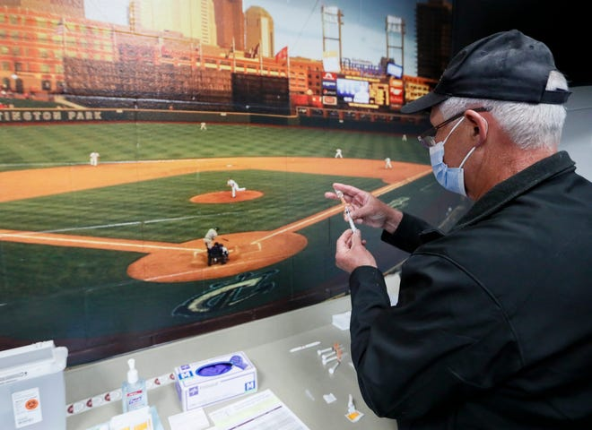 Mount Carmel pharmacist David McKenney measures doses of a Johnson & Johnson COVID-19 vaccine in the first aid station on the main concourse during the Columbus Clippers' opening day Triple-A baseball game at Huntington Park in Columbus, Ohio, on May 11, 2021. 39 people received a Johnson & Johnson vaccination from Mount Carmel during the event.