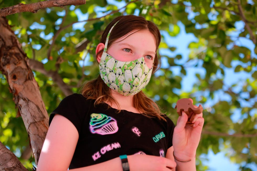 Rose Uberuaga, 12, poses with a 3D-printed plastic elephant she designed remotely during a camp last summer in Santa Fe, New Mexico.