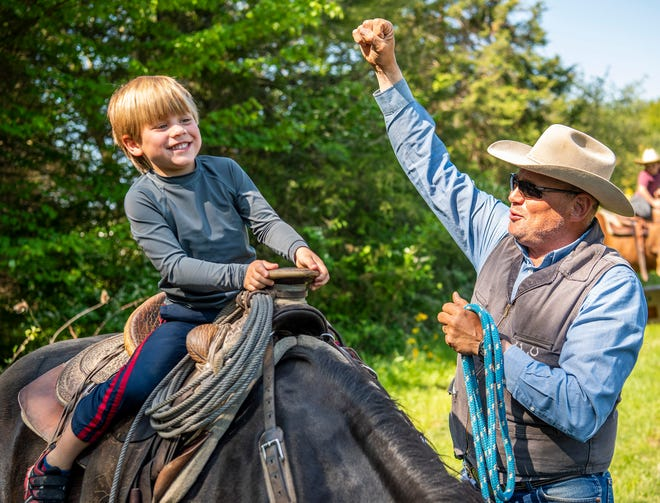 """Stone Creek Ranch's Wayne Allbright raises his arm in victory Friday as Cedars Christian School's Jude Cochran gets himself onto a horse. The activity was part of the school's book day in honor of the children reading """"Little Britches"""" by Ralph Moody. (Rich Janzaruk / Herald-Times)"""