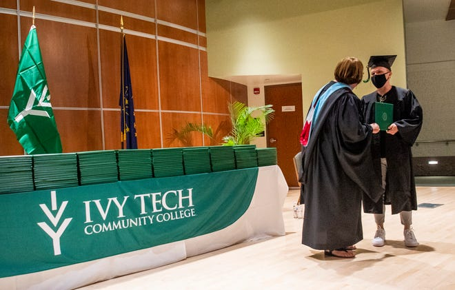 Graduate Tyler Warner gets his diploma May 15 from Ivy Tech Community College Chancellor Jennie Vaughan at the school's Bloomington graduation ceremonies.