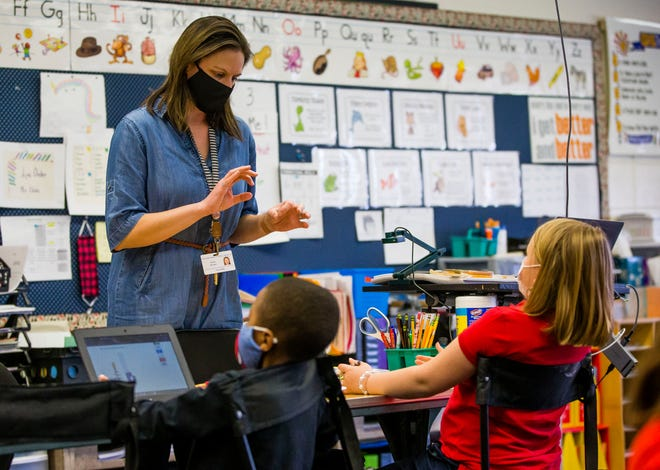 First grade teacher Nichole Blake works with some of her students Thursday, April 1, 2021 at Swanson Traditional School in South Bend.