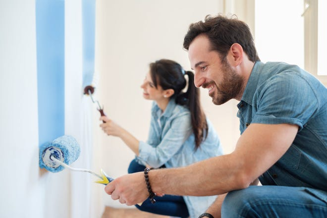 Two people paint a room together.
