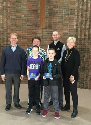 """Winners in the local '""""Rotary Four Way Test"""" essay contest were announced during chapel Friday morning at Watertown Christian School by members of the local Rotary Club. They are pictured front from left, second place winner Lucas Saraceni and third place winner Noah Wallenmeyer; back, Rotary President Reed Holien and Rotary members Nancy Weber, Sean Melmer and Brenda Engelhart. The winners received a desk plaque and check. (Courtesy photo)"""