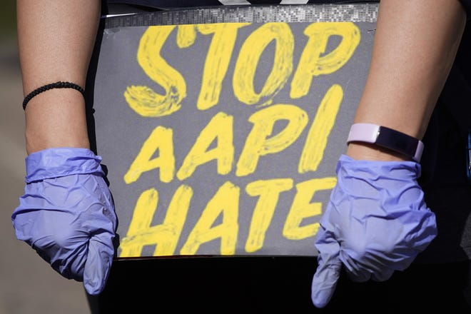 """FILE - In this March 20, 2021, file photo, woman holds a sign and attends a rally to support stop AAPI (Asian Americans and Pacific Islanders) hate at the Logan Square Monument in Chicago. After more than a year filled with attacks on Asian Americans unfairly blamed for the coronavirus, a majority of Americans across racial and ethnic groups believe anti-Asian American discrimination has worsened over the last year. A poll from the The Associated Press-NORC Center for Public Affairs Research finds nearly half of Americans believe Asian Americans encounter """"a great deal"""" or """"quite a lot"""" of discrimination. (AP Photo/Nam Y. Huh, File)"""