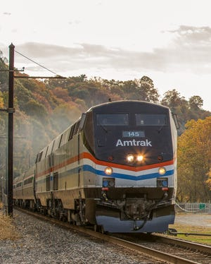 An 18-year-old woman was killed when she was hit by an Amtrak train while walking along the tracks, authorities said.