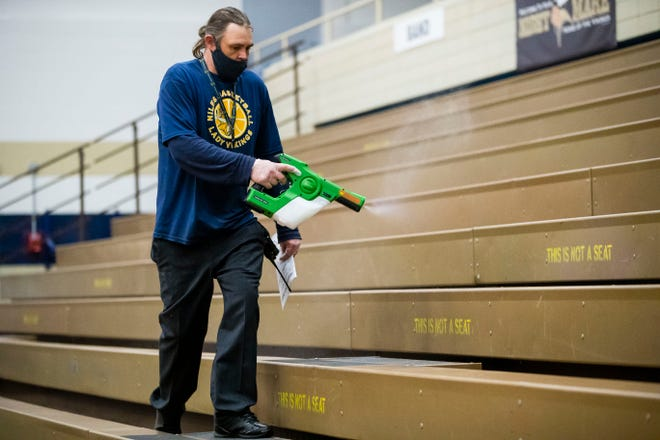 Nathan Thomas sanitizes stands between district semifinal basketball games on March 25, 2021, at Niles High School.