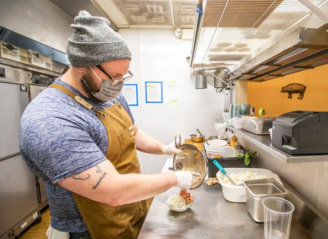 Zack Kidd prepares a poke dish inside the new Poke Hale pop-up restaurant on Monday at the Prized Pig in Mishawaka.