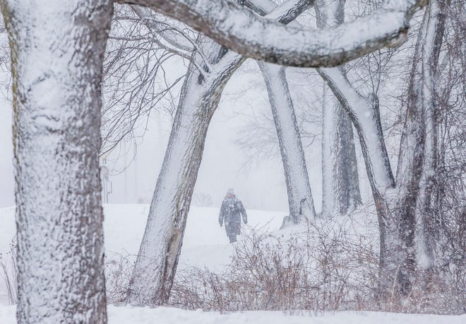 Tina Velthuizen, of South Bend, walks along the Riverside Trail during a heavy burst of snow on Thursday in South Bend.