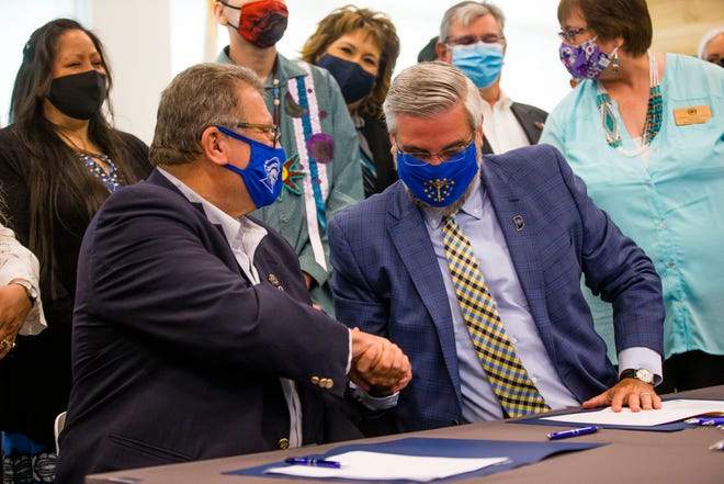 Indiana Governor Eric Holcomb shakes hands with Tribal Council Chairman Mathtew Wesaw after completing a ceremonial signing to conclude the State of Indiana's approval process of the Class III Gaming Compact between Indiana and the Pokagon Band of Potawatomi Tuesday, May 4, 2021 at Howard Park in South Bend.
