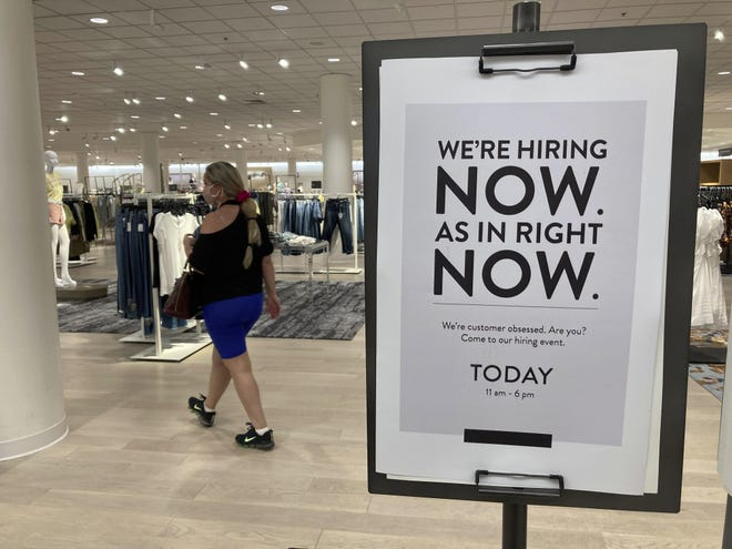 A customer walks behind a sign at a Nordstrom store seeking employees on Friday in Coral Gables, Florida. The number of Americans seeking unemployment benefits dropped last week to 406,000, a new pandemic low and more evidence that the job market is strengthening as the virus wanes and economy further reopens.