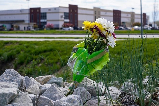 A single bouquet of flowers is placed across the street from the FedEx facility in Indianapolis, where eight people were shot and killed on April 15.
