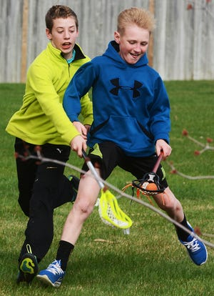 Camdyn Rieffenberger (left) tries to knock the ball from stick of his cousin Jake Bramer during a contest in Jake's backyard. The two boys were burning off some post-Easter dinner energy. Camdyn is the son of Ryan Rieffenberger and Nicole Rieffenberger, and Jake is the son of Travis and Heather Bramer, all of Watertown.