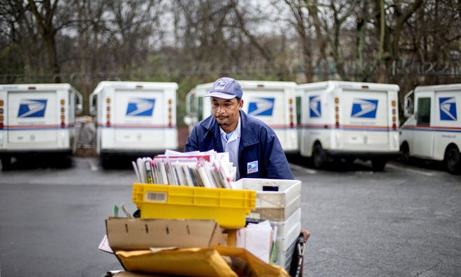 A U.S. Postal Service letter carrier gathers mail to load into his truck in Atlanta.