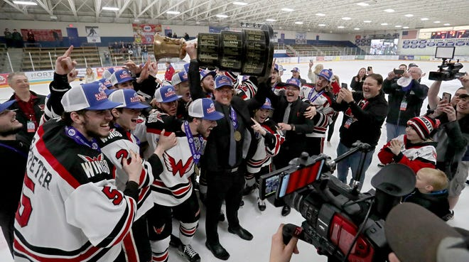 Aberdeen Wings head coach Scott Langer, center, hoists the Robertson Cup trophy while surrounded by the team after the Wings won the title with a 2-1 win over the Fairbanks Ice Dogs Tuesday night at the Fogerty Ice Arena in Blaine, Mn. American News photo by John Davis taken 5/14/2019