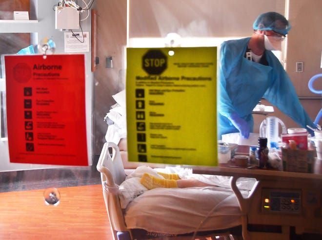 Seen through a protective glass door, a critical care nurse attends to a COVID-19 patient in the intensive care unit at Holmes Regional Medical Center in Melbourne on May 12.