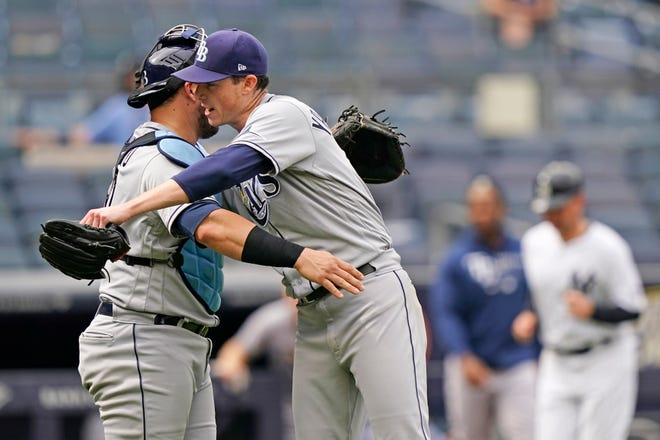 Tampa Bay Rays catcher Mike Zunino, left, congratulates Rays starting pitcher Ryan Yarbrough, center, with an embrace after Yarbrough pitched a complete baseball game in the Rays 9-2 victory over the New York Yankees, Thursday, June 3, 2021, at Yankee Stadium in New York. (AP Photo/Kathy Willens)