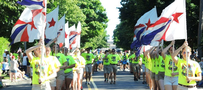 Members of the Petoskey Marching Band Color Guard march in an earlier year's Fourth of July parade. (file photo)