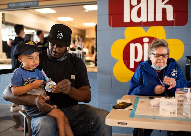Montelle Walcott Jr., 2, enjoys a lollipop while dad Montelle Walcott receives a Johnson & Johnson COVID-19 vaccine from Eileen McKeon ahead of the first Worcester Red Sox game with no COVID-19 restrictions on Tuesday, June 1, in Worcester, Mass.