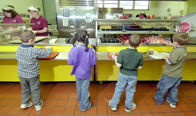 Elementary school students stand in line to receive their lunch.