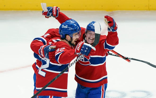 Montreal Canadiens' Erik Gustafsson, left, celebrates his goal with teammates Cole Caufield and Nick Suzuki (obscured) during first-period NHL Stanley Cup playoff hockey action against the Winnipeg Jets in Montreal, Monday, June 7, 2021. (Paul Chiasson/The Canadian Press via AP)