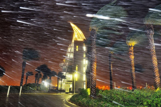 Trees sway from heavy rain and wind from Hurricane Matthew in front of Exploration Tower in Cape Canaveral in 2016.