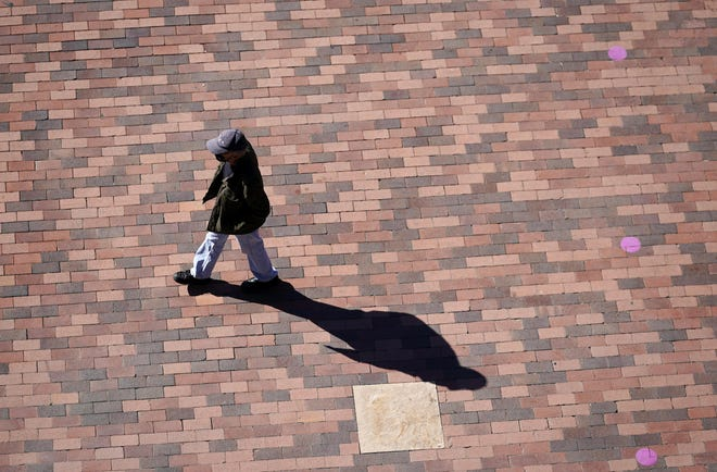FILE - In this April 8, 2021, file photo a lone pedestrian casts a long shadow while passing through the plaza in front of the gate top Coors Field at the corner of 20th Street and Blake early in Denver. Millions of Americans are struggling through life with few people they can trust for personal and professional help, a disconnect that raises a key barrier to recovery from the social, emotional and economic fallout of the pandemic. That's according to a new poll from Impact Genome and The Associated Press-NORC Center for Public Affairs Research. (AP Photo/David Zalubowski, File)