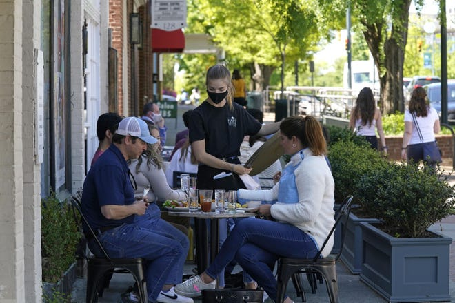 Patrons are assisted while dining along a sidewalk on Franklin Street in Chapel Hill, N.C., Friday, April 16, 2021. As consumers increasingly venture away from home, demand has begun to shift away from manufactured goods and toward services, from airline fares to restaurant meals, triggering inflation in those areas. (AP Photo/Gerry Broome)