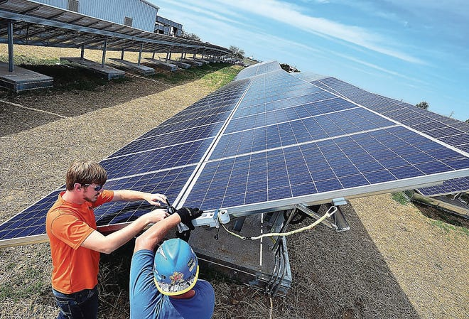 Pfister Energy Project Manager Steven Beall, left, and technician Brennnan Kuels, test solar modules Wednesday at Horizon Goodwill. A new program offered by Ottawa County will allow local businesses to access long-term loans for making improvements related to energy consumption.