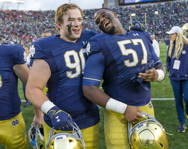 Notre Dame offensive lineman Hunter Spears, left, announced Thursday he has medically retired from football. Pictured, Spears celebrates with defensive tackle Jayson Ademilola following Notre Dame's 2019 victory over Virginia.