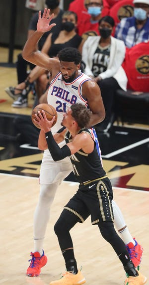 Atlanta Hawks guard Trae Young, bottom, draws a foul from Philadelphia 76ers center Joel Embiid, top, on his way to the basket during Game 4 of a second-round NBA basketball playoff series on Monday, June 14, 2021, in Atlanta. (Curtis Compton/Atlanta Journal-Constitution via AP)