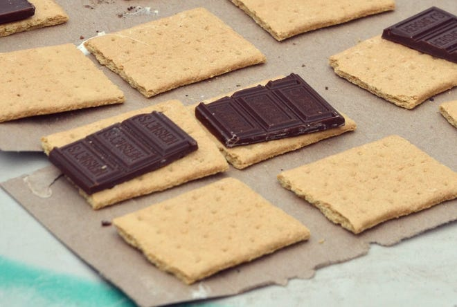 Chocolate and graham crackers are ready for hot marshmallows to be added.