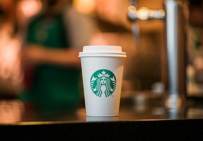 A coffee cup displays the Starbucks logo.