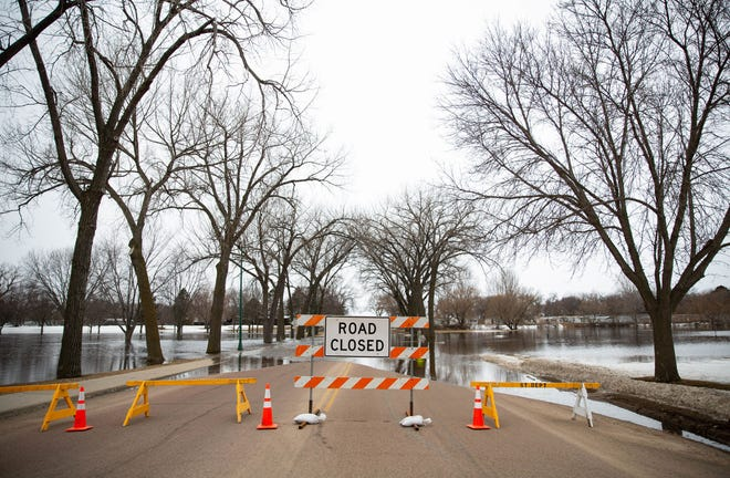 The Watertown Street Department has closed 10th Avenue NW Thursday due to waters from the Big Sioux River flowing over the road. (Public Opinion photo by Grace Ramey)