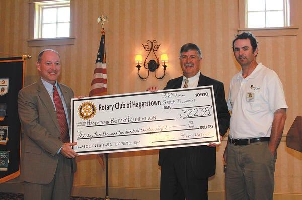 Hagerstown Rotary Golf Tournament co-chairmen Tim Harner, center, and Randy Finn, right, present a check to Hagerstown Rotary (Downtown) President Chris Motz, left.