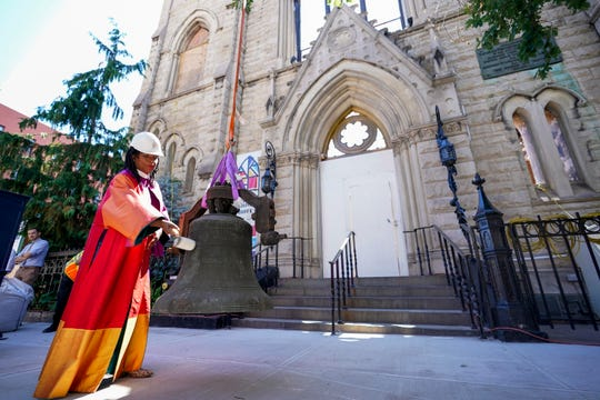 Senior Minister the Rev. Jacqueline J. Lewis rings New York's Liberty Bell after a construction crew lowered it from Middle Collegiate Church's bell tower on Wednesday in the East Village neighborhood of New York. The bell was discovered intact in the historic church after it was gutted by a six-alarm fire in December 2020.
