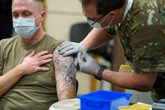 Nurse Jose Picart administers Staff Sgt. Travis Snyder's first dose of the Pfizer COVID-19 vaccine at Madigan Army Medical Center at Joint Base Lewis-McChord in Washington state, south of Seattle, on Dec. 16, 2020.