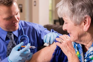 A medical professional administering a vaccine to an elderly person.