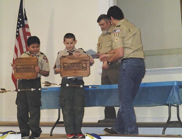 Pictured are Scot Arasmith (Cubmaster) and Noel Macias (Webelos leader) presenting the plaques and awards.