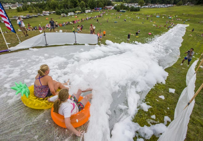 Two people prepare to slide at Slide the Hill in August at George Wilson Park in Mishawaka in 2019.