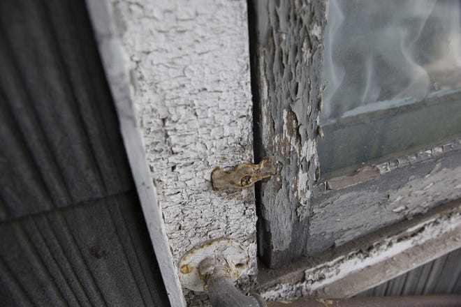 Chipped lead paint surrounds a window.