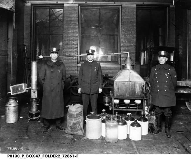 I poliziotti dell'Indiana stanno con apparecchiature di distillazione illegali al momento durante il proibizionismo.  Apre la mostra dell'Indiana Historical Society