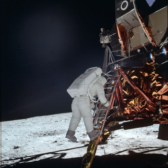 In this July 20, 1969, photo made available by NASA, astronaut Buzz Aldrin Jr. descends a ladder from the Lunar Module during the Apollo 11 mission. Neil Armstrong was the first from the mission to step on the moon.